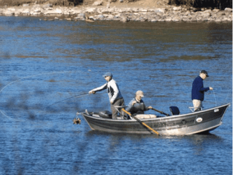 Three fly fishermen fishing from a a drift boat