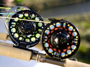 """Einarsson fly reels on fly rods on a rack - It makes the most durable fly reel components by far and it is the most expensive. The reel components are literally """"carved"""" out of one solid piece of metal. The is why a reel manufactured this way has a higher cost and toughness. Side note here: There are a myriad of different protective coatings that are often proprietary to each brand. The coating protects the reel from denting, corrosion and cracking. Coating technologies among reel makers are very similar but the thicker the coating the tougher the reel will be."""