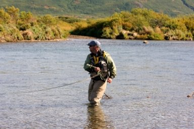 A fly fisherman in Alaska setting the hook, downstream and across the current