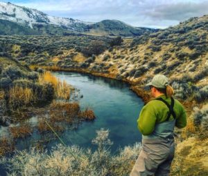 A fly fisherwoman standing over a desert spring creek watching for rising trout