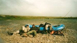 Four fly fishermen lying behind a raft on a gravel bar in Alaska to get out of the wind.