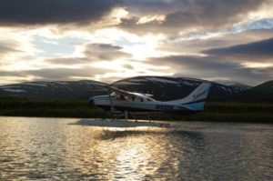 A 206 Cessna taxiing across a lake in Alaska