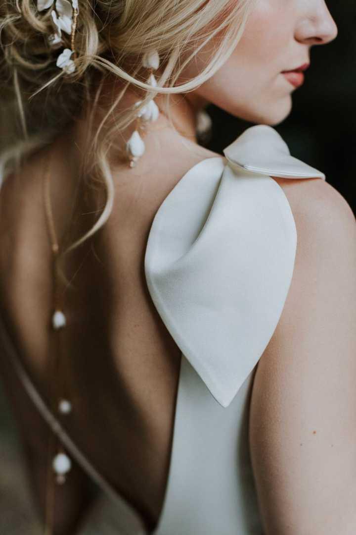 back of bride showing petal shoulder detail on wedding dress with gold back necklace
