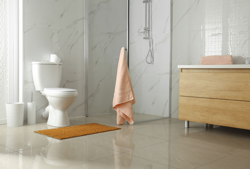 Toilet bowl near shower stall in modern bathroom interior