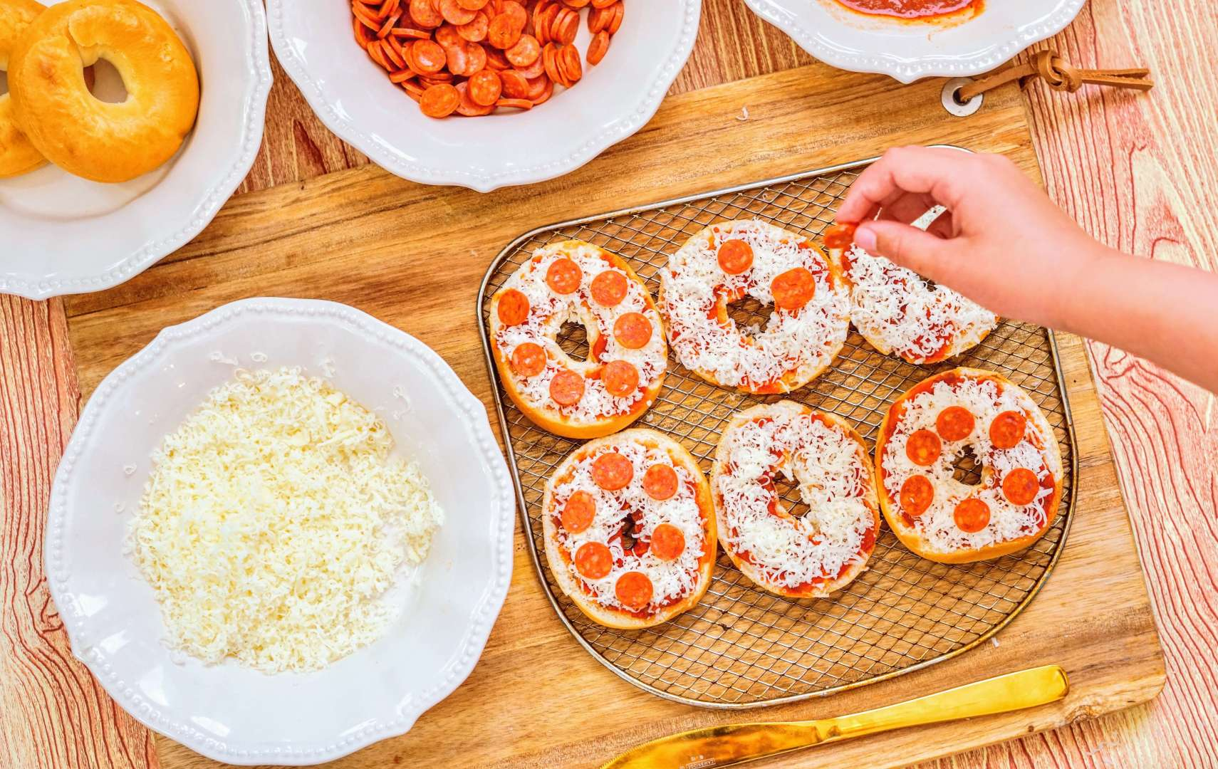 adding pepperoni to pizza bagels