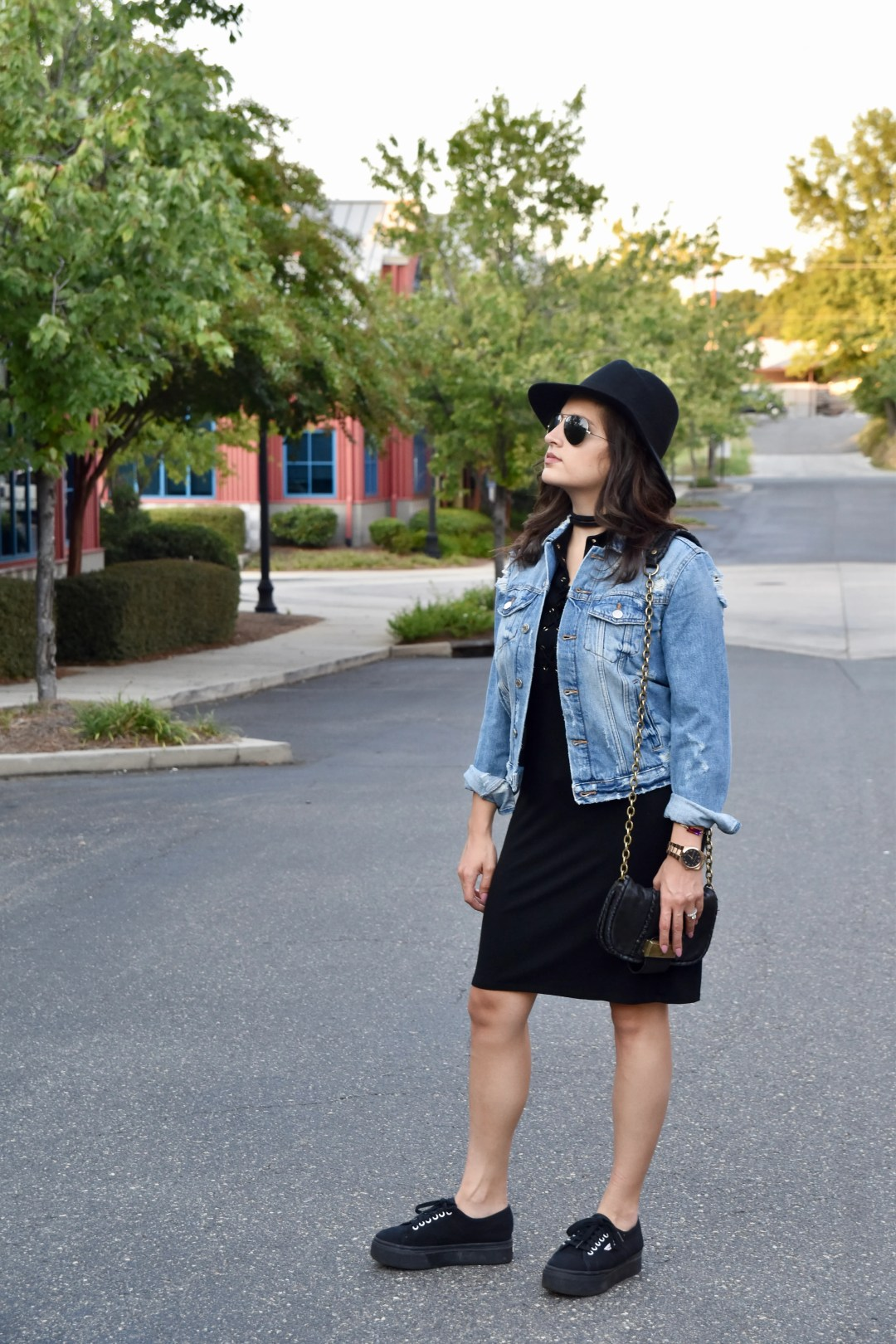 Dania outfit post in black dress, superga, jean jacket, and hat