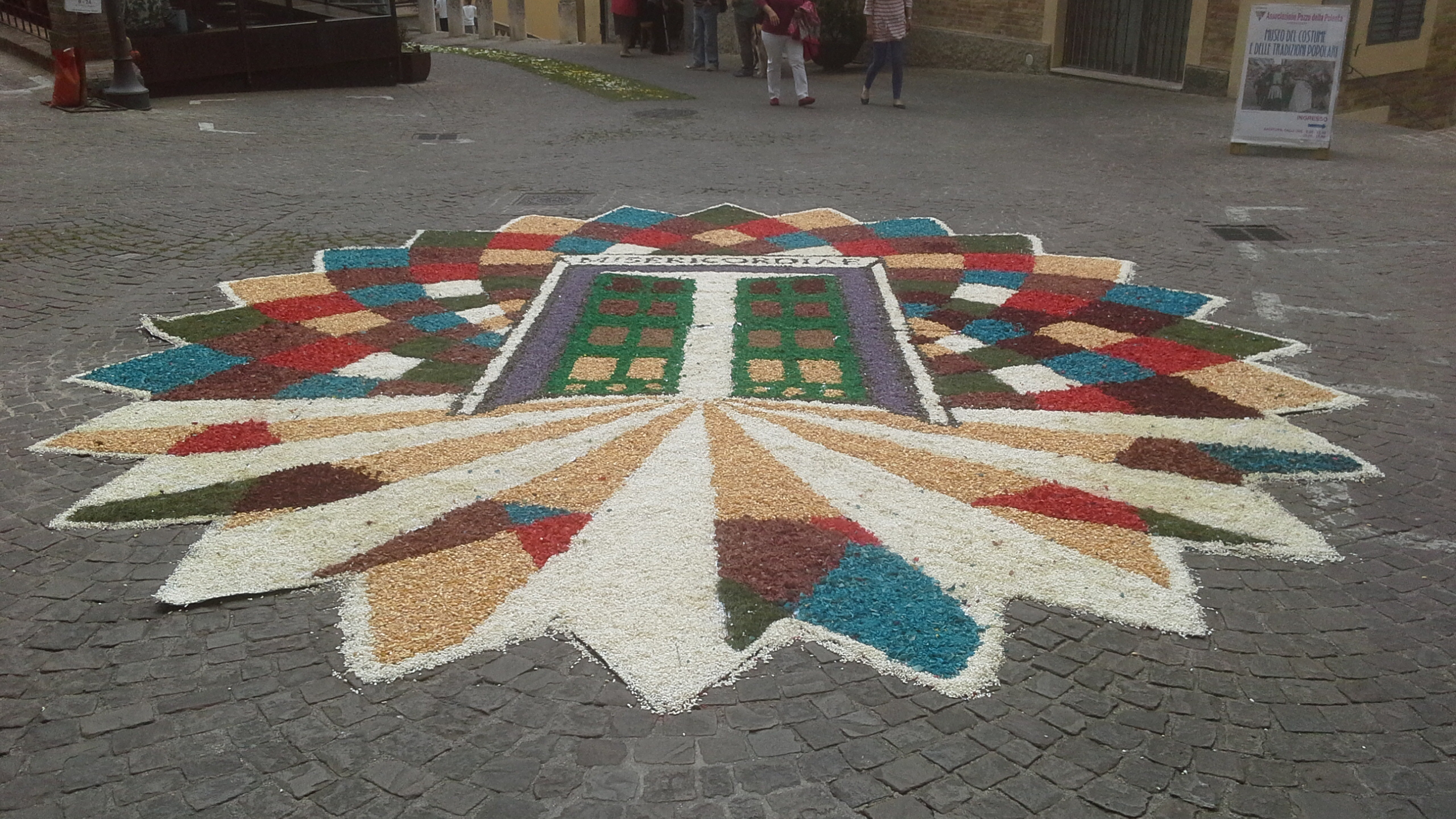 The Englishwoman admires Corinaldo's Infiorata and walks in the Corpus Christi procession