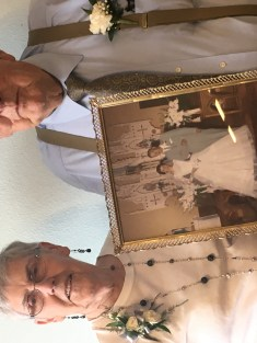 A man and a woman pose with a picture from their wedding day
