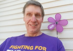 A man smiling next to a purple flower pinwheel