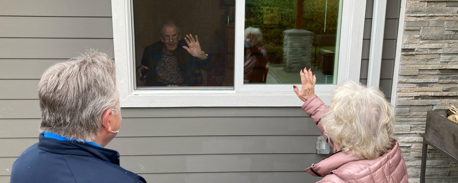 Bill and his neighbor look through the window at a loved one