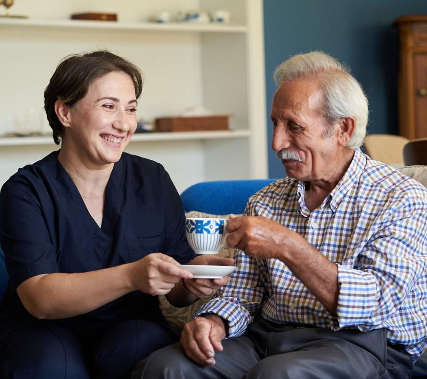 A woman serving a man tea