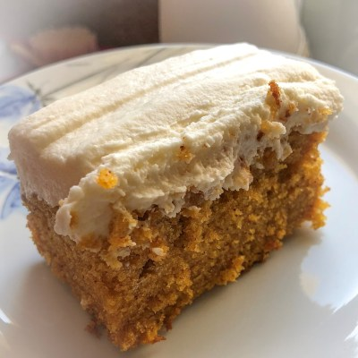 A moist, soft, orange pumpkin bar covered with a layer of thick, white frosting sits atop a white plate.