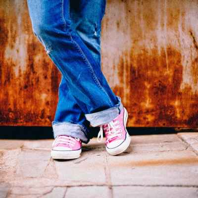 A woman stands against a rusty wall with jeans on and pink Converse tennis shoes with her legs crossed.