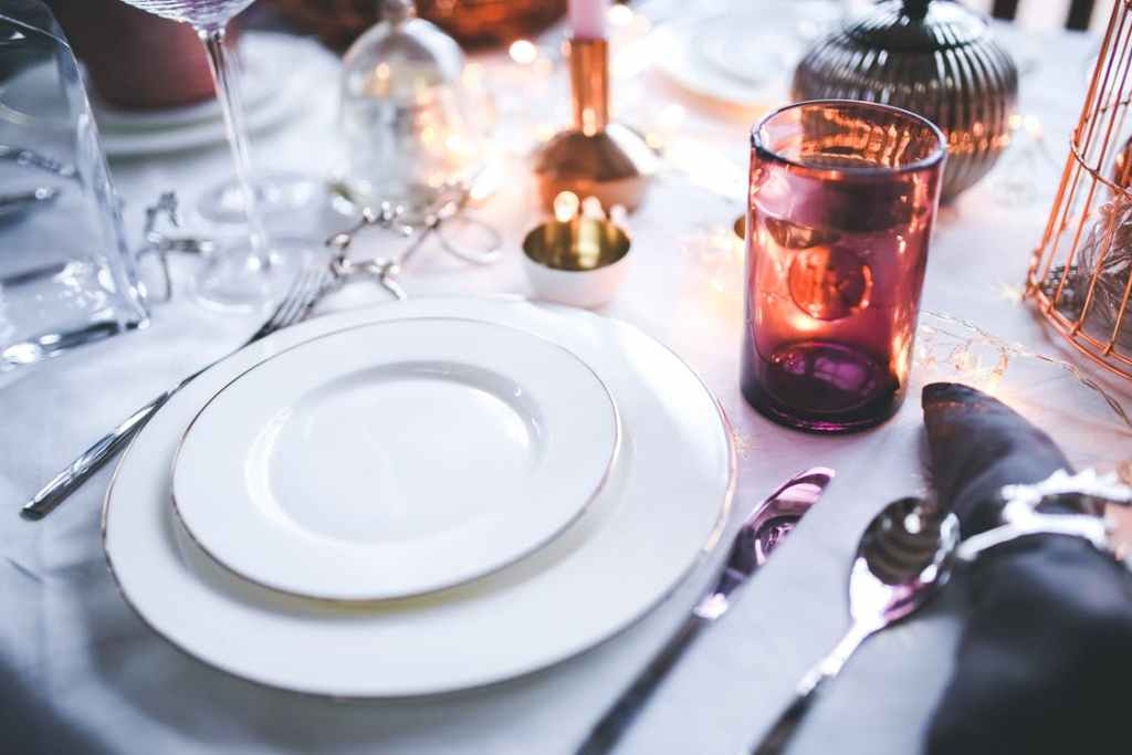 Place setting at a table including white linens, white plates, shiny silverware and a candle for ambiance.