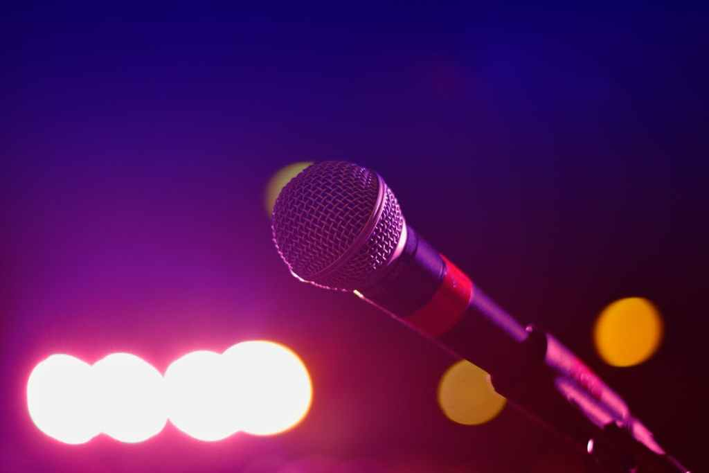 A close up of a microphone against blurred stage lighting.