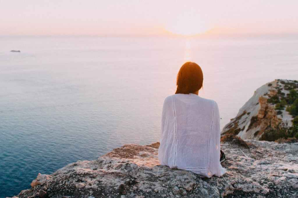 A young woman sits atop a cliff with a white shawl wrapped around her shoulders, looking out of over the water gazing into the sunset practicing mindfulness.