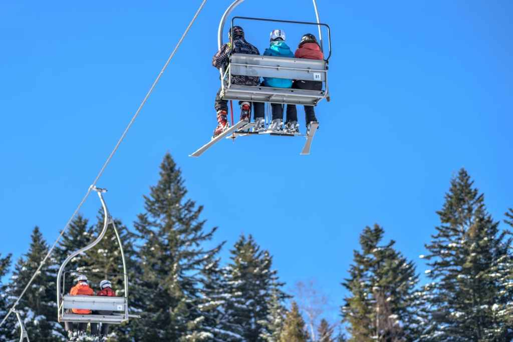 Three people sitting on the ski lift heading up the mountain.