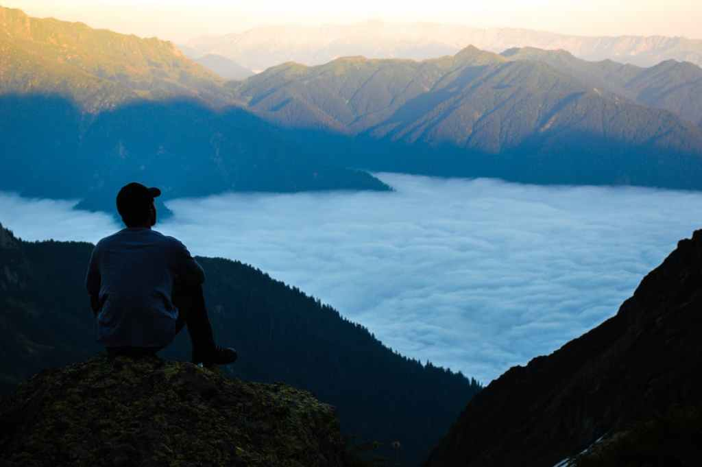 Man sitting on top of a mountain he just climbed, looking over the side down at the water. Anxiety.