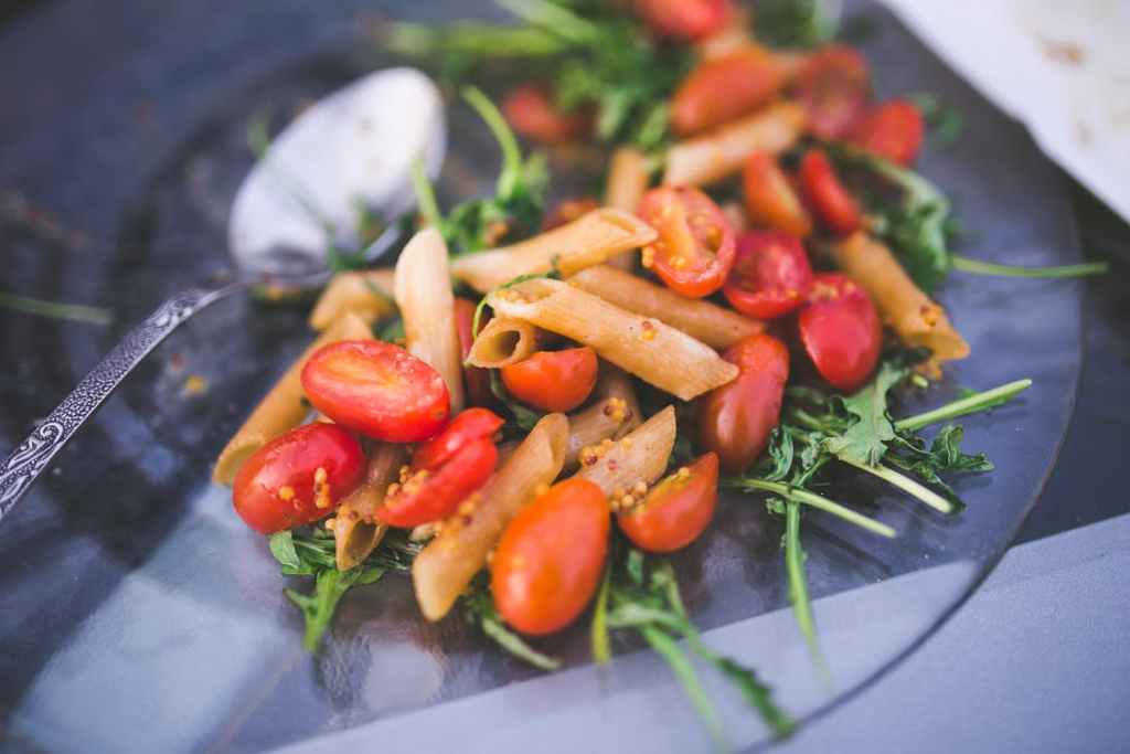 Ziti pasta sits on top of a bed of baby arugula and cherry tomatoes, Weight Watchers Freestyle