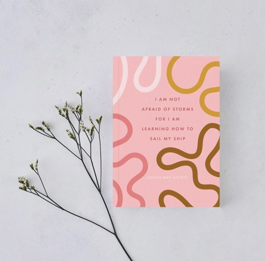 "Literary Inspired Gifts Pink journal with a ""I AM LEARNING HOW TO SAIL MY SHIP"" quote from Louisa May Alcott's Little Women."
