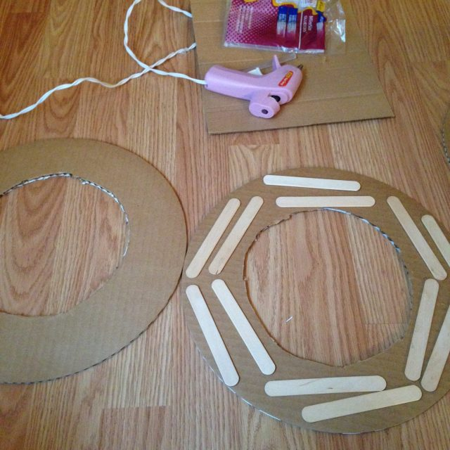 Hot glue popsicle sticks to one side of the cardboard for added support