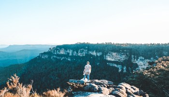 Woman standing on edge overlooking blue mountains