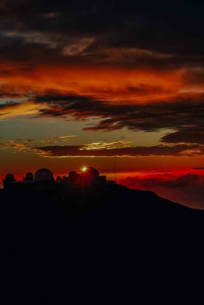 The sun setting behind the observatory, turning the sky bright orange and red