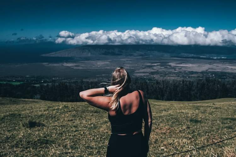 Woman in workout shirt and pants holding her hair, looking out to the coastline from the top of Haleakala