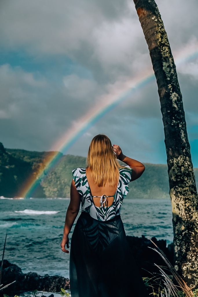Woman standing in a swimsuit and skirt wrap next to a palm tree, looking out to the ocean to see a rainbow