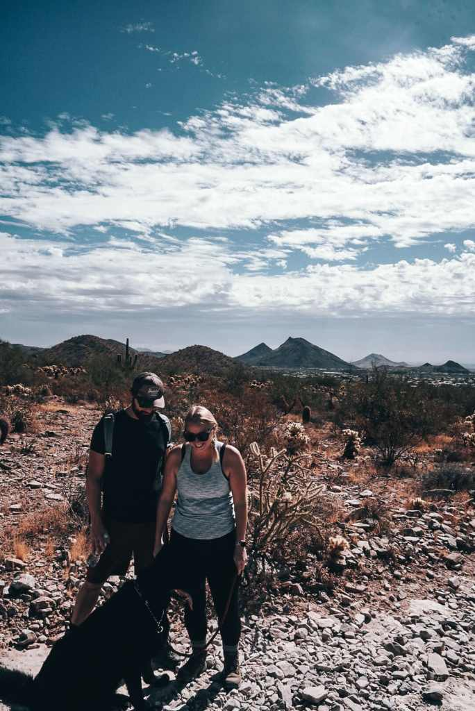 Woman, man, and German Shepherd standing in the Scottsdale hiking trail of the dog Wash trail