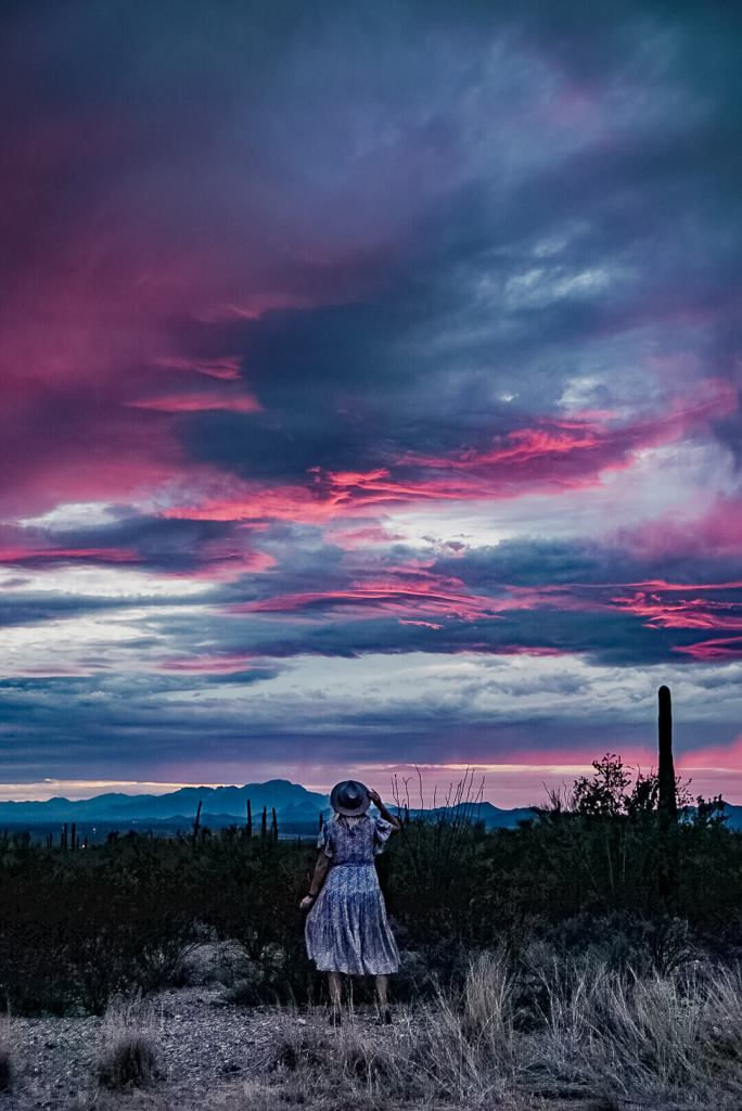 Woman in a dress standing amid the sand and cactus looking at the hot pink and purple sunset