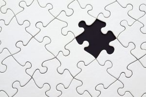 A white puzzle with one missing piece.