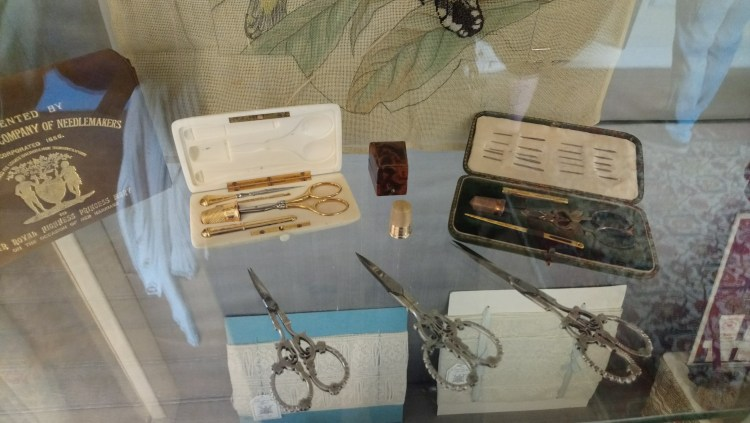 Vintage sewing tools, such as thimbles, needle-cases and decorative scissors on display at Harewood House, Yorkshire