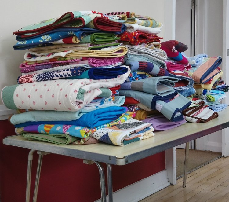 a pile of quilts on a table, all made to give away
