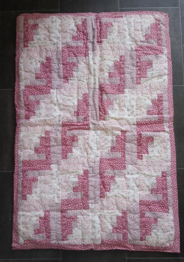 a cot quilt made using log cabin blocks in shades of pink