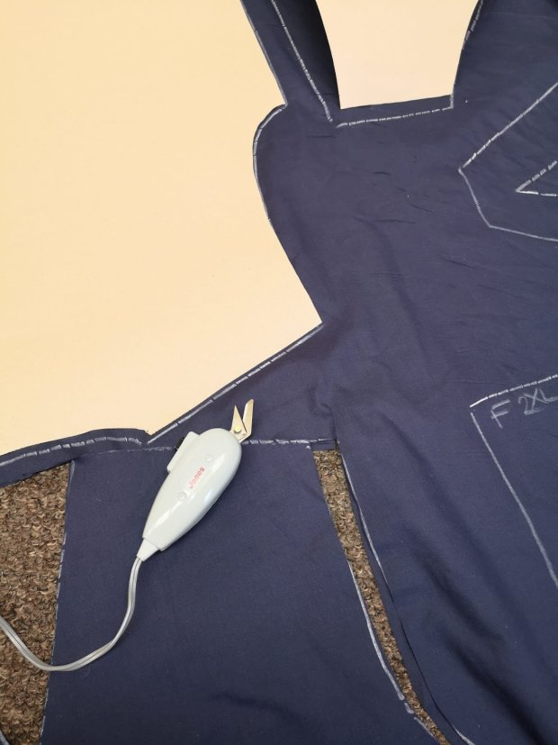 fabric being cut out to make hospital scrubs