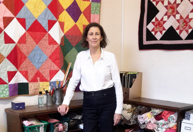 Amanda Jane Ogden in her studio with quilts on the wall: 'Colours of Mexico' (left) and 'Winter Roses' (right)