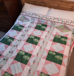 a double-bed quilt in pink, dark green, pale aqua and white, entitled 'summer Bouquets' by Amanda Jane Textiles