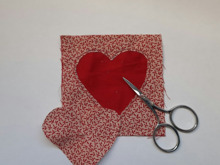 reverse applique tutorial, cutting round the inside of the shape