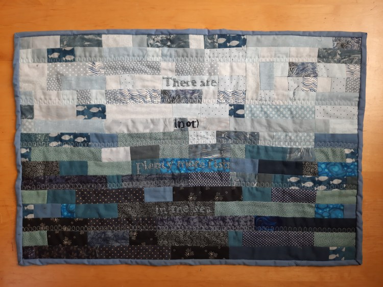 'There are {not} plenty more fish in the sea' by Amanda Jane Ogden, small quilt composed on blue blocks, a few with fish in and the wor