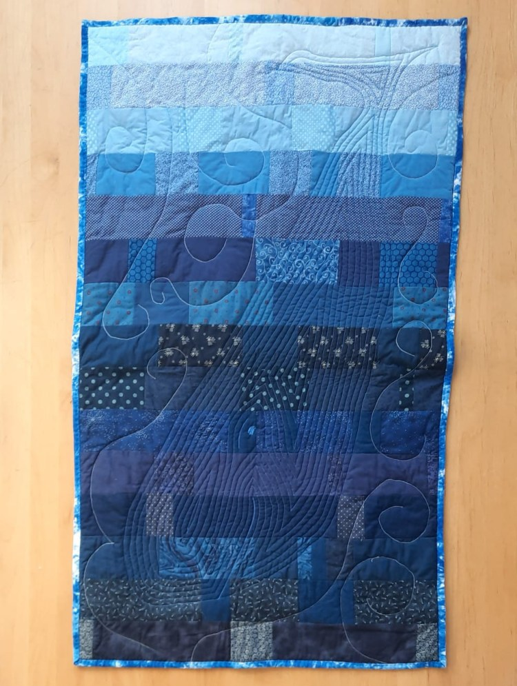 'Now you see her, now you don't' quilted wall-hanging by Amanda Jane Ogden, depicting a diving whale quilted onto a background of blue rectangles