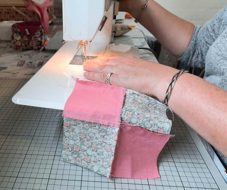 a person learning a new craft,  stitching a patchwork block in pink-coloured fabrics on the 'Quilt in a Day' course