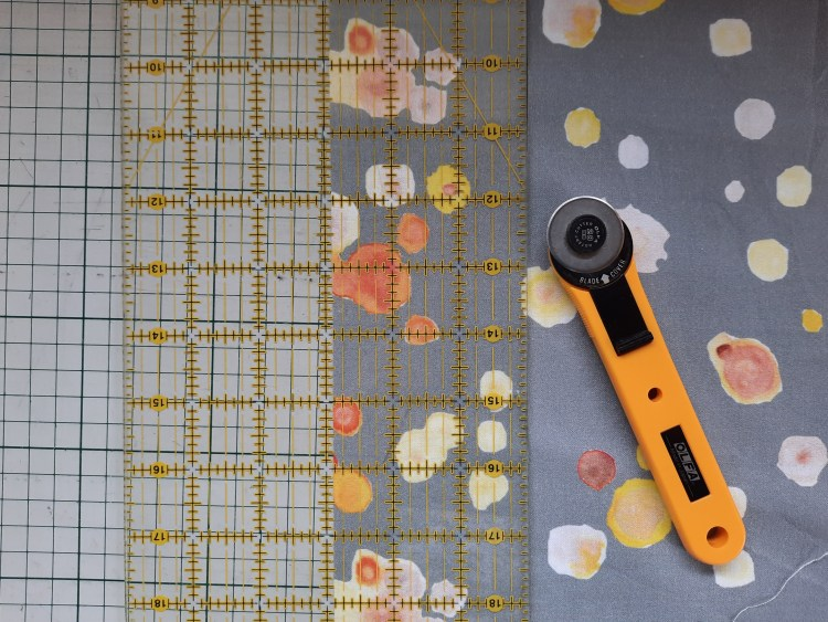 Cutting a two and seven-eighths inch strip from 'Micro-organisms' fabric by Amanda Jane Textiles, using a quilter's ruler and rotary cutter