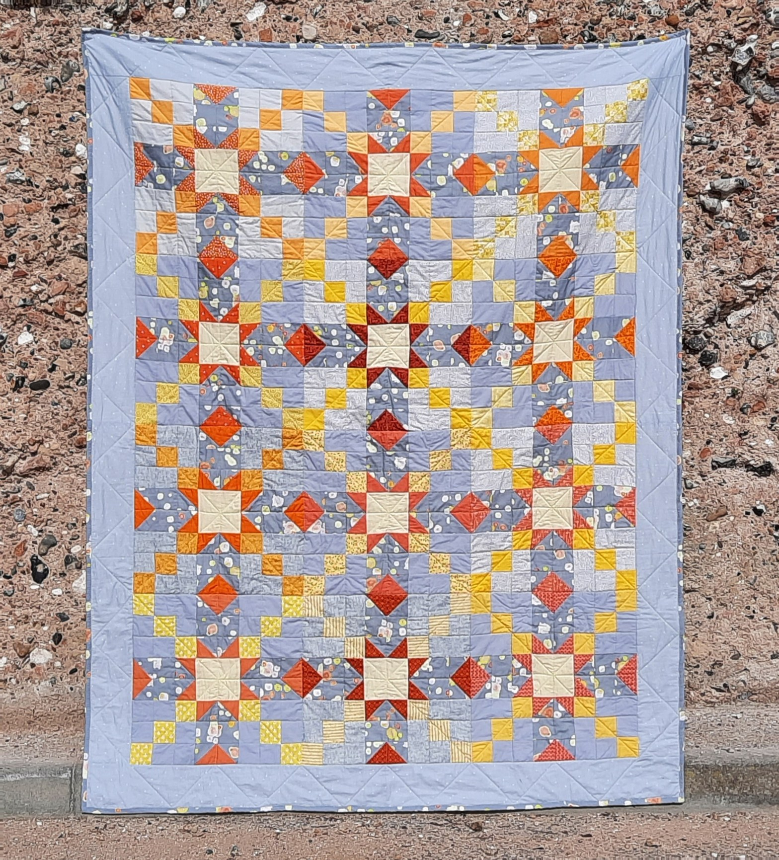 'Starstruck' quilt by Amanda Jane Textiles, the quilt contains twelve star blocks with pale yellow centres and orange arms, each of these lead out with a burst of yellow squares to the next one. The feature fabric around the stars is 'Micro-organisms' by Amanda Jane Textiles on Spoonflower. Other squares are pale grey and there is a light grey border.