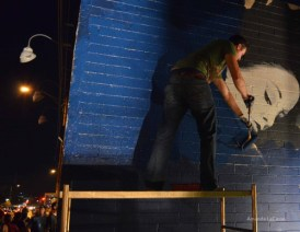 Joe Pagac paints over the former mural on the east side of Eye Lounge gallery in preparation for a new mural.