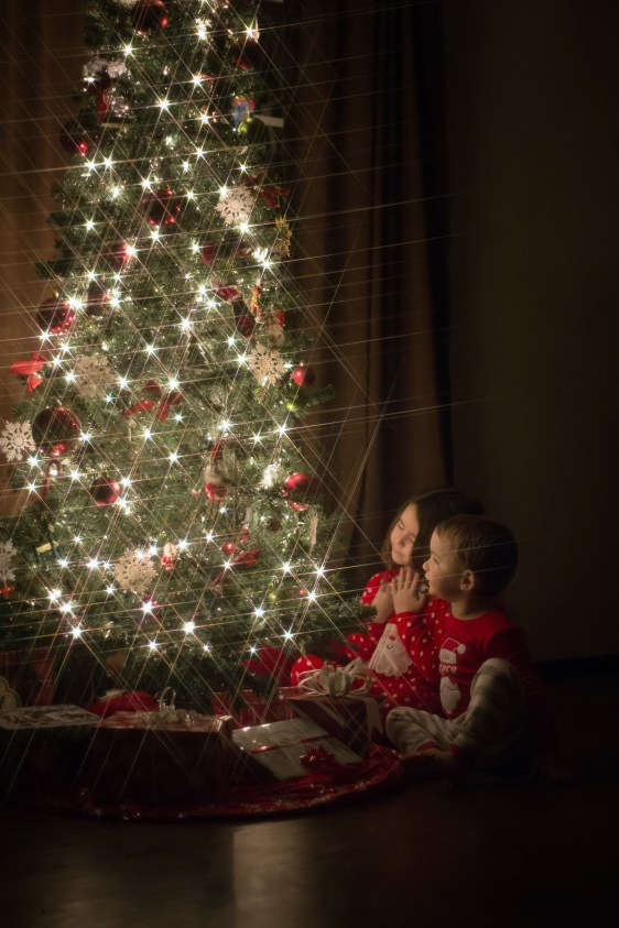 children in red christmas pajamas sitting next to christmas tree