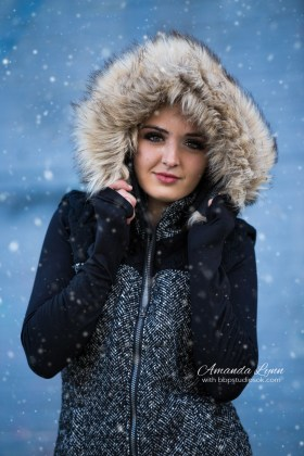 high school senior girl wearing fluffy coat standing in snow automobile alley oklahoma city