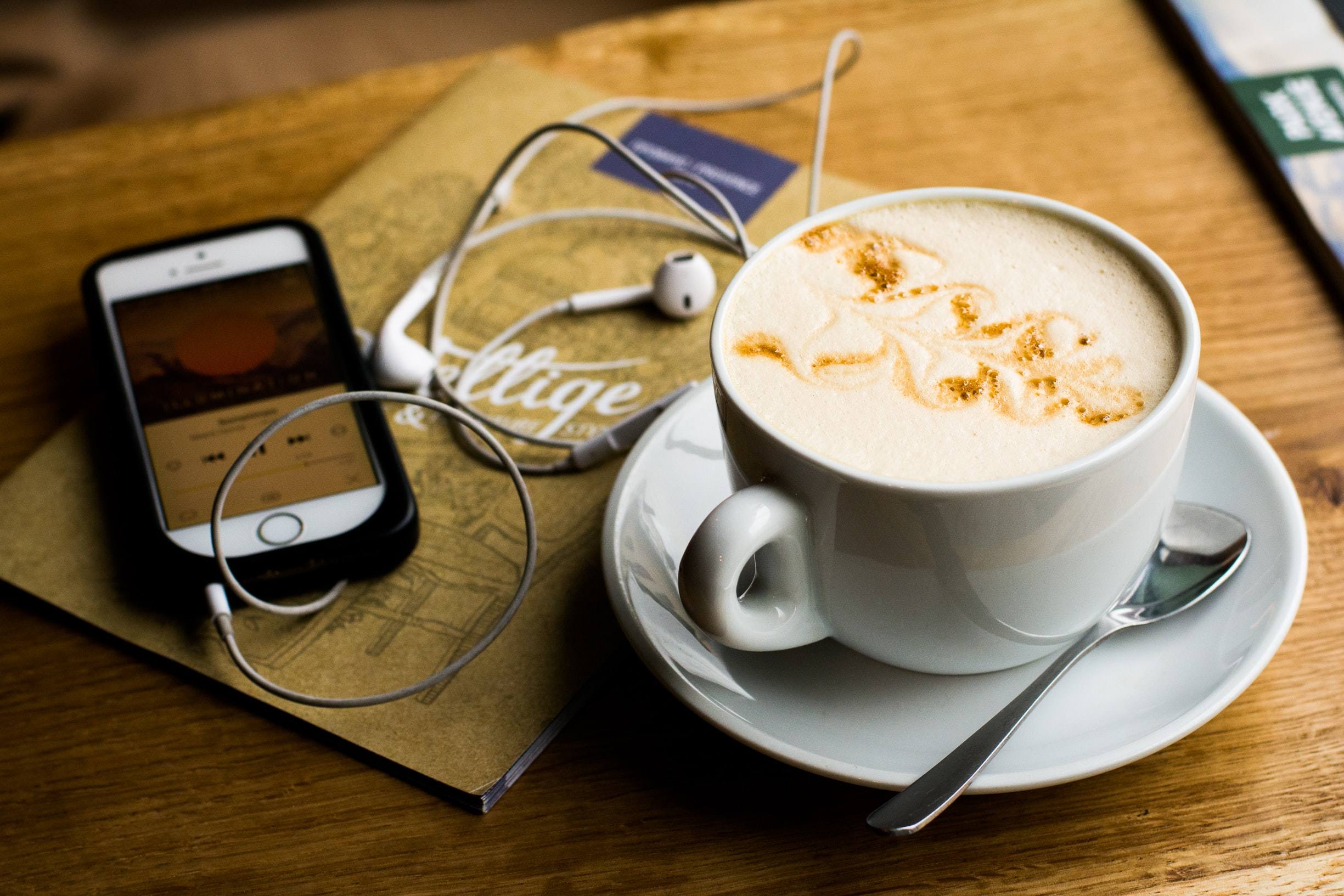 An espresso next to a phone and headphones on a table.
