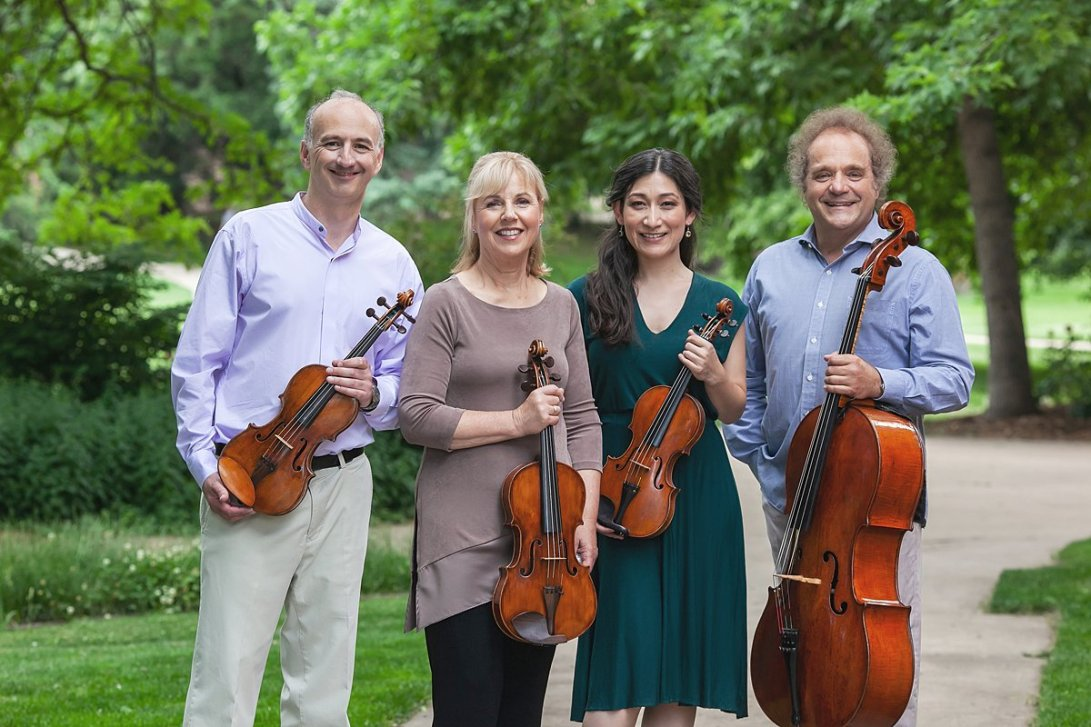 Four people smiling with string instruments