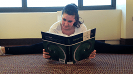 Double majoring in dance and biology, Alex Dombroski catches up on reading while stretching.